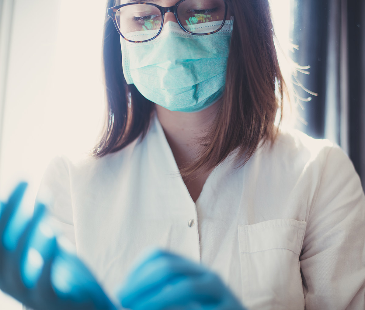 medical-nurse-putting-on-blue-sterilized-surgical-gloves-picture-id1223524759